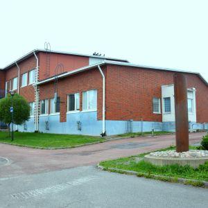 Stor skolbyggnad i tegel med skylt utanför. Gräsplätt kring byggnaden och stengrund under skylten. Ett trafikmärke syns också på bilden. Intill byggnaden en trottoar i röd sten och bilväg.
