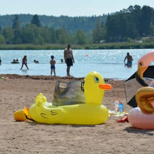 Uppblåsbara badleksaker på en strand med människor i bakgrunden.