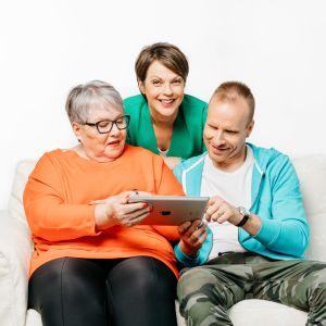 Oranssissa paidassa oleva nainen ja Mikko Kekäläinen istuvat sohvalla ja katsovat tablettia. Anna-Liisa Tilus seisoo takana, katsoo kameraan ja hymyilee.