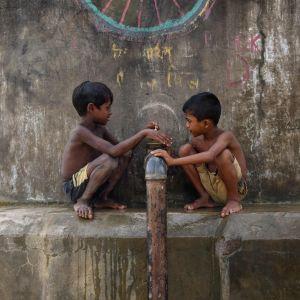 Pojkar vid vattenledning i flyktinglägret Nayapara nära Cox's Bazar  i Bangladesh