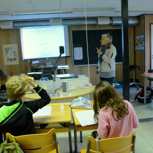 Elever som sitter i en klass och blir undervisade av en lärare.