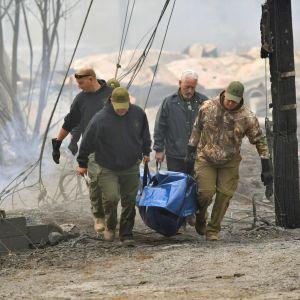 Poliser bar bort en kropp från ett utbränt bostadshus i staden Paradise på lördagen.