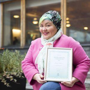 Kuvassa on hymyilevä nainen pinkissä takissa, ja hän pitää sylissään Hyvän mielen lähettiläs - tunnustustaulua.