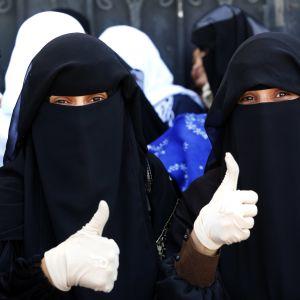 Två kvinnor i Jemens huvudstad Sanaa visar tummen upp för planerade fredssamtal i Sverige den här månaden