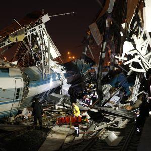 Räddningspersonal intill söndertrasad tågvagn och vad som ser ut att vara en trasig brokonstruktion vid järnvägsstationen Marşandiz i Ankara 13.12.2018.
