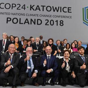 Medlemmarna på klimatkonferensen i Katowice visar upp glada miner efter att konferensen lidit mot sitt slut