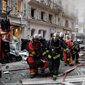Brandmän bär bort en skadad person efter lördagens explosion i centrala Paris.