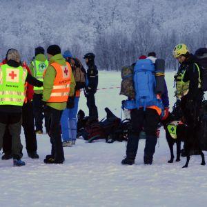 Ett gäng med räddningsmanskap står vid ett fjäll.