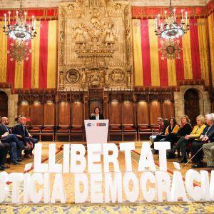 Barcelonas borgmästare Ada Colau talar inför en banderoll med texten Frihet, rättvisa, demokrati