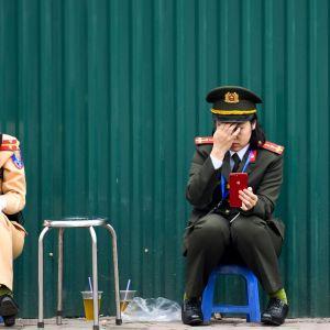 Två vietnamesiska poliser vilar sig nära Hotel Melia i samband med toppmötet i Hanoi 28.2.2019
