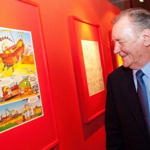 Asterix -sarjakuvan piirtäjä ja käsikirjoittaja Albert Uderzo katselee sarjakuvasivua, joka on seinällä
