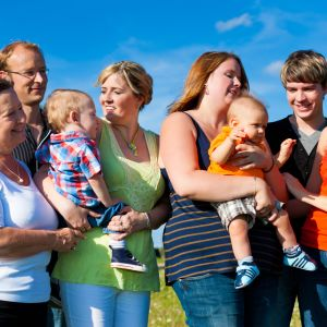 En stor familj med småbarn står ute på en äng på sommaren