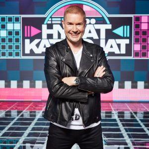 Hyvät katsojat -ohjelman juontaja Marco Bjurström hymyilee kameralle ohjelman lavasteissa.