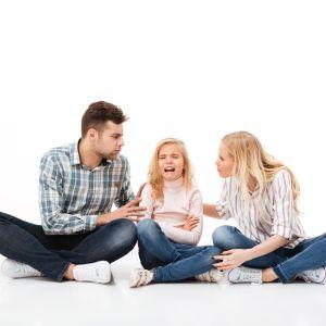 en mamma och pappa sitter på golvet och försöker diskutera med sin dotter som gråter