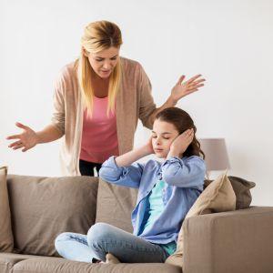 en mamma grälar med sin dotter som sitter på soffan och håller för öronen