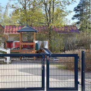 Gården på ett daghem. En stängd järngrind och inne på gården ser man en rutsckana och en klätterställning som liknar ett hus.