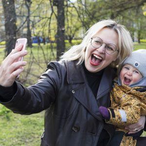 Catariina Salo tar en glad selfie tillsammans med sitt barn som hon har i famnen.