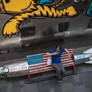 En man i Beijing sitter på en bänk under sin shoppingrunda.