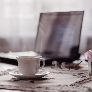 Tietokone ja höyryävä kahvikuppi pöydällä.