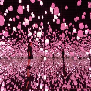 Ihmiset seisovat vaaleanpunaisten lamppujen keskellä