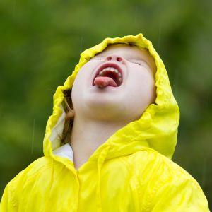 Flicka iklädd gul regnjacka räcker ut tungan och fångar regndroppar.