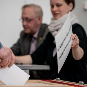 Äänestystä Helsingissä taustalla vaalivirkailijat Susanna Lappalainen ja Seppo Hölttä