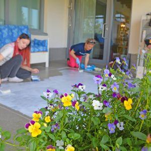 Två kvinnor målar en trasmatta på ett golv på en balkong.