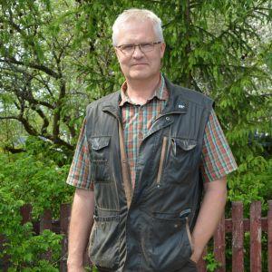 Man med glasögon, skinnväst och skjorta framför sommargrönskande skogsdunge.