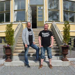 Två leende män står framför en trappa.