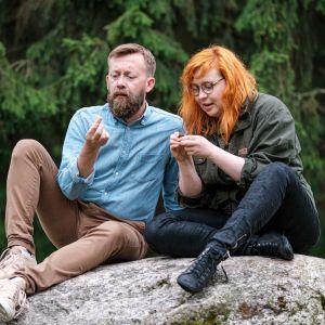 Naturväktarnas programledare Annika Ljungberg och Joakim Lax sitter på en sten.