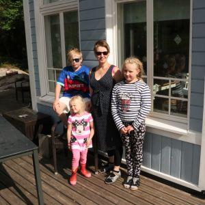 Rosa Pentikäinen-Mattila står med sina barn i solskenet ute på terassen och tittar mot kameran.