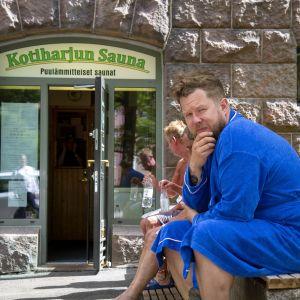 Samae Koskinen istuu vilvoittelemassa kaupunkisaunan ulkopuolella sinisessä kylpytakissa ja katsoo kameraan.