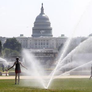 Två kvinnor svalkar sig under vattenspridare på gräsmattan framför Kapitolium i Washington DC under en extrem värmebölja i juli 2019.