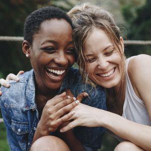 Ystävykset pitävät toisiaan kädestä nauraen.