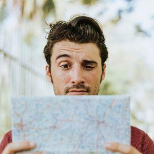 Mies katsoo tutkailevasti käsissään olevaa paperikarttaa.