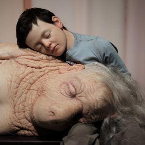 Konstverk: en far/morförälder sover i sitt barnbarns famn.
