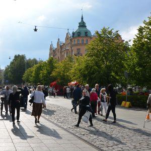 Människor går på en gågata i solsken.
