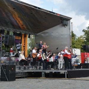 En orkester spelar på en utomhusscen.
