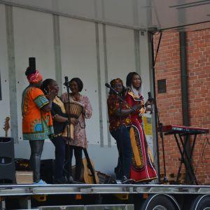 Fem kvinnor i färgglada kläder sjunger på en scen.