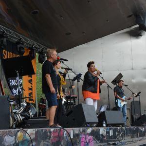 Personer sjunger på en scen.