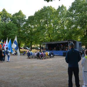 Personer står med flaggor vid en scen i en park.
