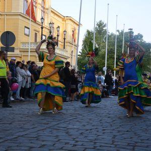 Kvinnor i färglada dräkter dansar på gatan.