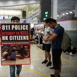 En demonstrant hålle rupp en plakat inne i flygplatsen i Hongkong.