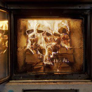 Ved brinner i eldstad med nätlucka framför.