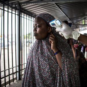 Granskning av en kvinnas kroppstemperatur på en granskningsplats i Kongo i juli 2019.