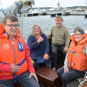 Fyra personer med flytväst i båt.
