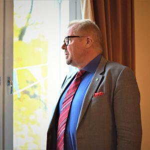 Man i grå kavaj och röd slips ser ut genom ett fönster.