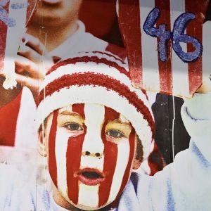 Plansch med röda och vita ränder och en barn som håller i skyltar med siffran 46.