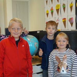 Två pojkar och tre flickor på rad i ett klassrum framför en jordglob på katedern