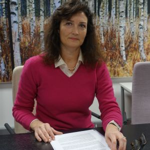 Direktören för den juridiska servicen på Migrationsverket Tirsa Forssell läser rapport som ligger på bordet framför henne
